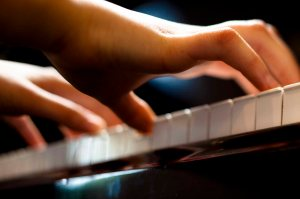 Closeup of a child's hands playing the piano. Horizontally framed shot.